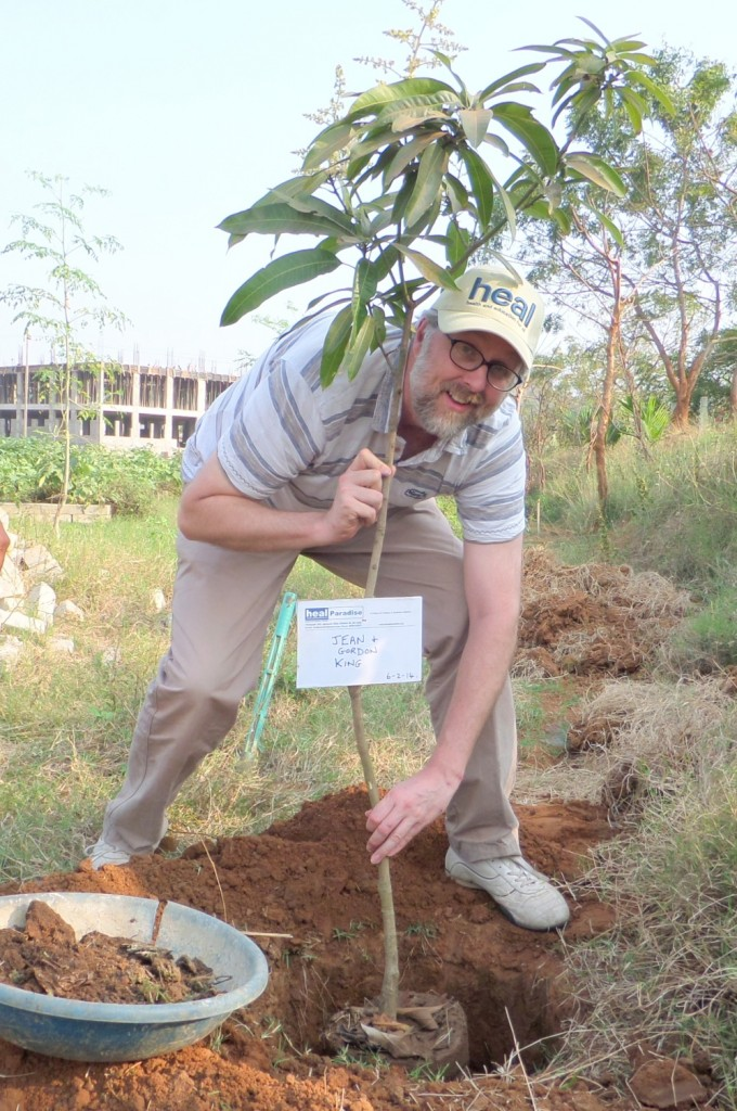 Jem King plants a mango tree, carrying a plaque with the name of his mother and father
