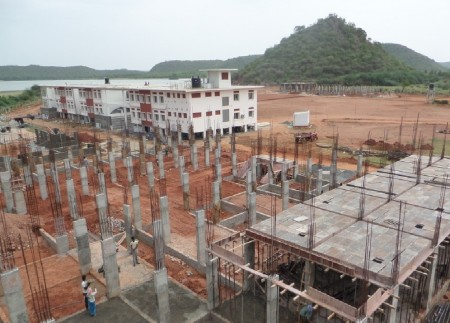Construction work progressing at HEAL Paradise Village, with the primary school building in the background